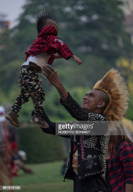 A member of a punk group plays with his oneyearold son as he and some of his friends gather in a park in central Yangon on April 12 on the eve of the...