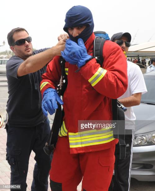A member of a Qatari rescue team puts protective gear on outside Doha's Villagio Mall after a fire broke out at the Gulf emirate's main shopping...