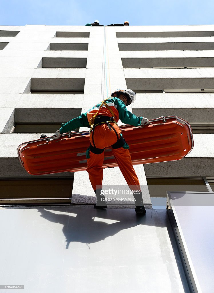 A member of a rescue team descends on a wall from the roof of a building as he holds a stretcher to carry an injured person during a disaster drill at Ginza shopping district in Tokyo on August 30, 2013. Some 5,000 people who live or work in the district, took part in the annual drill. AFP PHOTO/Toru YAMANAKA
