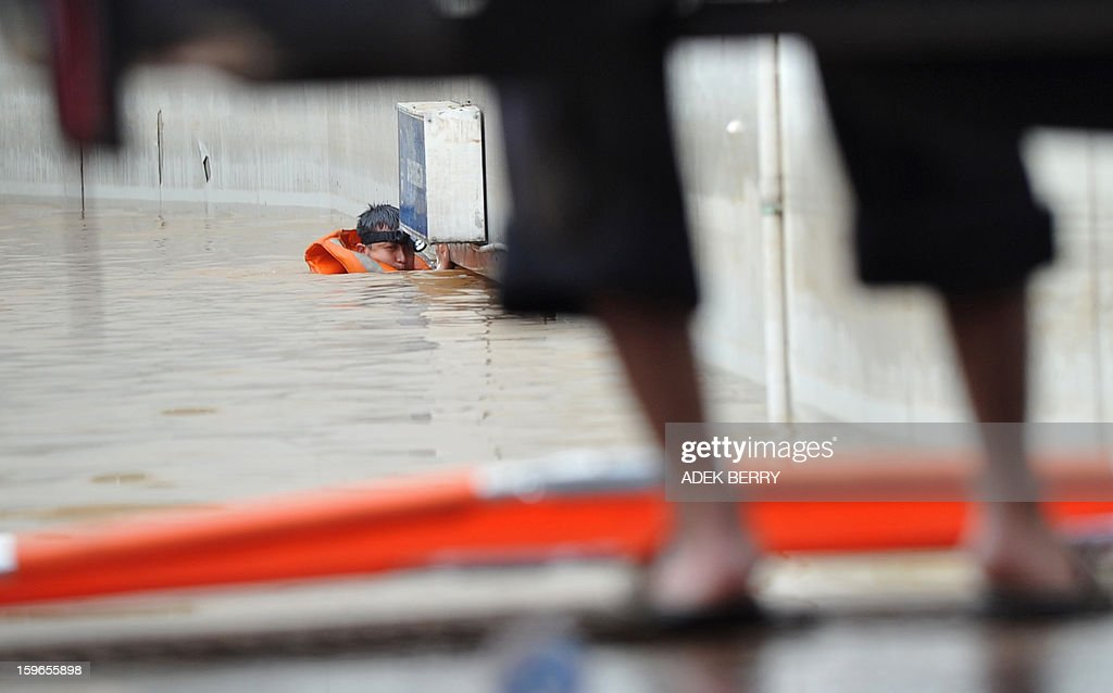 A member of a search and rescue team enters a gate at the base of the UOB building to help rescue people trapped in a basement after seasonal floods inundated much of downtown Jakarta on January 18, 2013. Floods in Indonesia's capital Jakarta have left at least 11 people dead and two missing, authorities said as murky brown waters submerged parts of the city's business district, causing chaos for a second day.