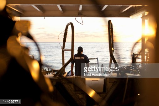 A member of a ship's crew looks out at the sunset : Stock Photo