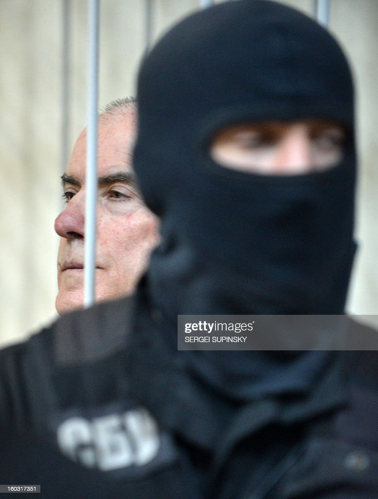 A member of a special police unit stands guard next to former chief of the external surveillance department of the Ukrainian Interior Ministry Oleksiy Pukach during the verdict reading of his trial for the murder of opposition journalist Georgy Gongadze in 2000, on January 29, 2013 at Kiev district court.