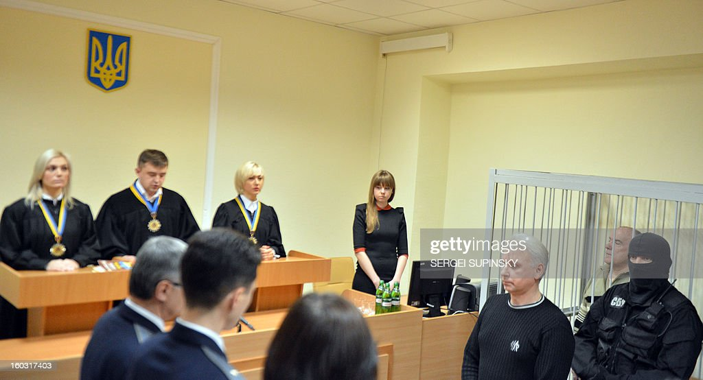 A member of a special police unit stands guard next to former chief of the external surveillance department of the Ukrainian Interior Ministry Oleksiy Pukach (2ndR) during the verdict reading of his trial for the murder of opposition journalist Georgy Gongadze in 2000, on January 29, 2013 at Kiev district court.
