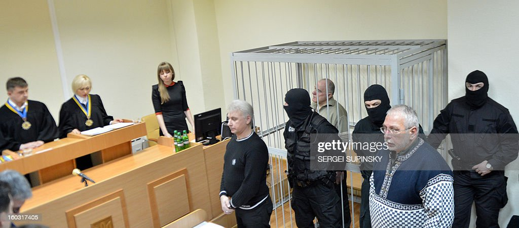 A member of a special police unit stands guard next to former chief of the external surveillance department of the Ukrainian Interior Ministry Oleksiy Pukach (4thR) during the verdict reading of his trial for the murder of opposition journalist Georgy Gongadze in 2000, on January 29, 2013 at Kiev district court.
