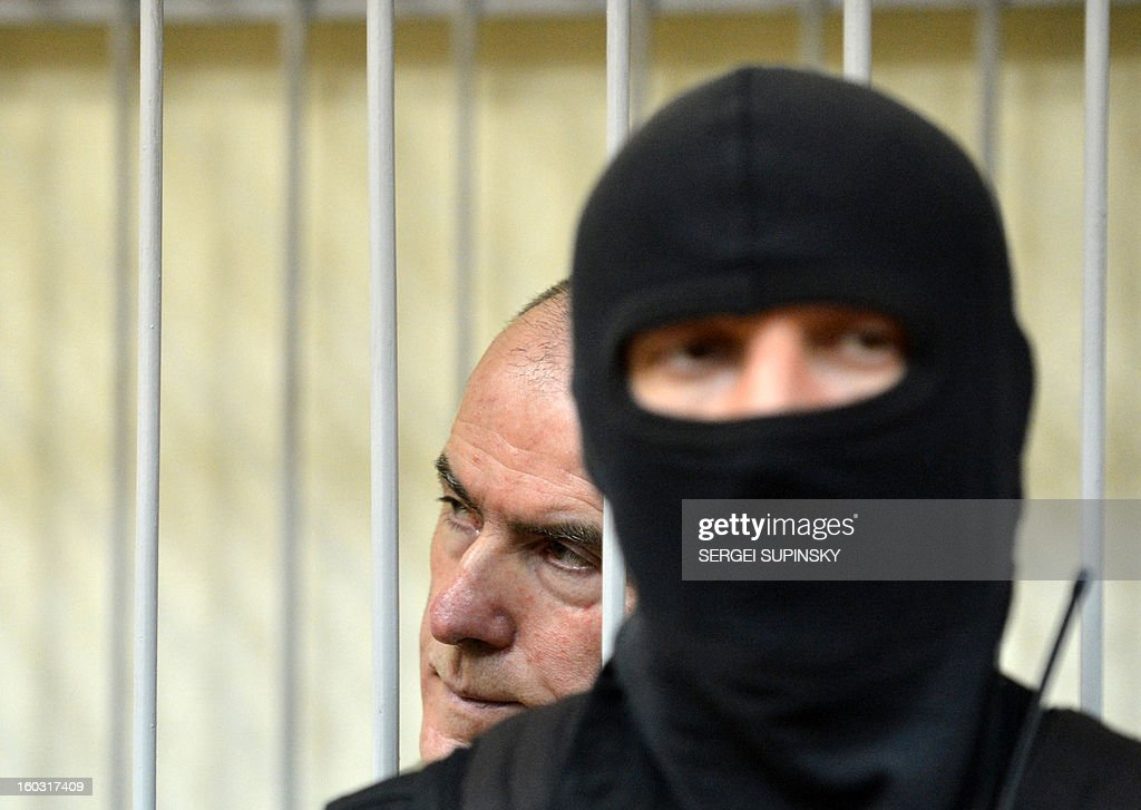 A member of a special police unit stands guard next to former chief of the external surveillance department of the Ukrainian Interior Ministry Oleksiy Pukach (L) during the verdict reading of his trial for the murder of opposition journalist Georgy Gongadze in 2000, on January 29, 2013 at Kiev district court.