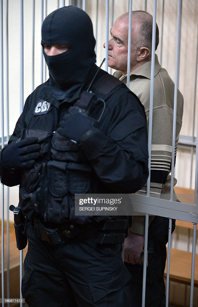 A member of a special police unit stands guard next to former chief of the external surveillance department of the Ukrainian Interior Ministry Oleksiy Pukach (R) during the verdict reading of his trial for the murder of opposition journalist Georgy Gongadze in 2000, on January 29, 2013 at Kiev district court.