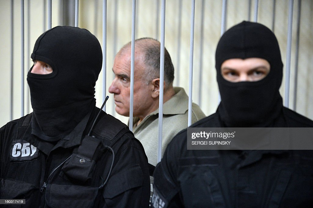A member of a special police unit stands guard next to former chief of the external surveillance department of the Ukrainian Interior Ministry Oleksiy Pukach (L) during the verdict reading of his trial for the murder of opposition journalist Georgy Gongadze in 2000, on January 29, 2013 at Kiev district court. AFP PHOTO/ SERGEI SUPINSKY