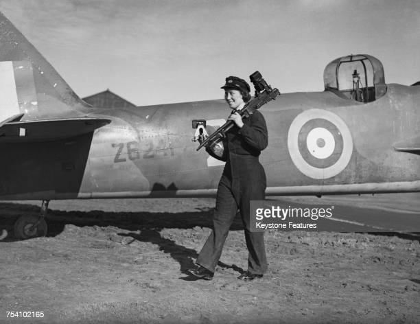 A member of a women's branch of the RAF carrying a machine gun from an aircraft 1st April 1942