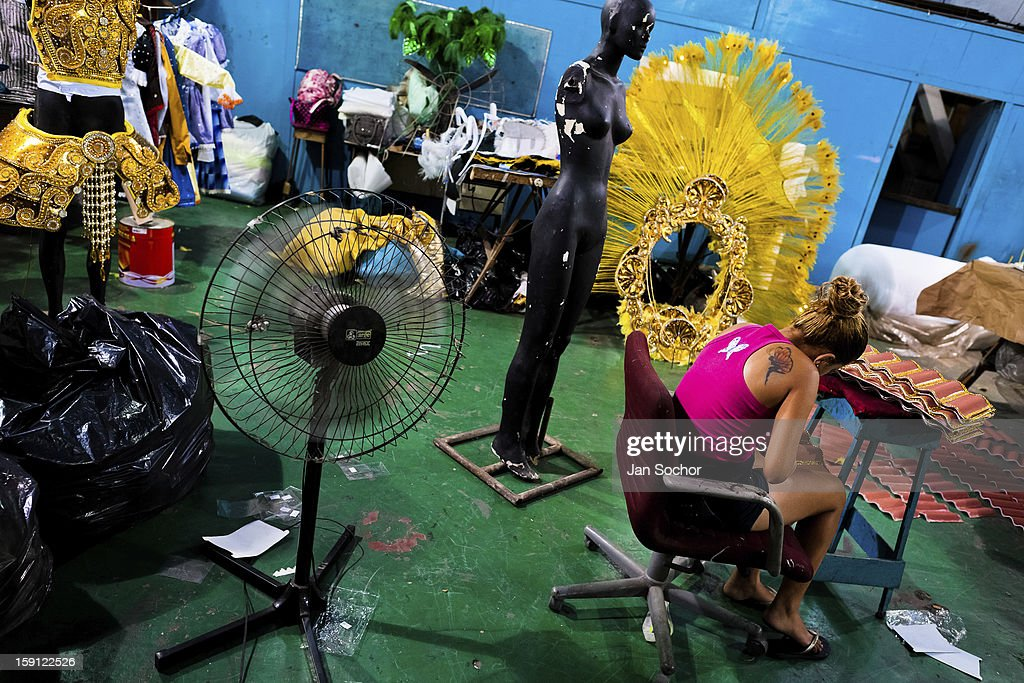 A member of Acadêmicos da Rocinha samba school arranges carnival costumes (fantasias, in portuguese) inside the workshop in Rio de Janeiro, Brazil, 15 February 2012. The carnival preparations start early in July or August, some 7-8 months before the main samba schools parade at the sambodrome. Samba schools hire teams of professional designers and artists who, according to the original theme selected by the school directors and then featured by the school during the parade, create allegorical floats, costumes, sculptures, music, choreography and the entire school show. However, the most of the everyday work in the carnival hangars is performed by unknown but fully dedicated samba schools members.