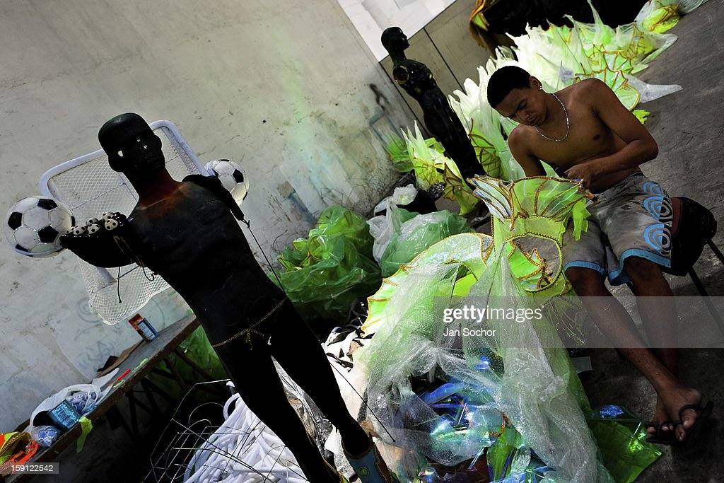 A member of Acadêmicos da Rocinha samba school arranges carnival costumes (fantasias, in portuguese) inside the workshop in Rio de Janeiro, Brazil, 14 February 2012. The carnival preparations start early in July or August, some 7-8 months before the main samba schools parade at the sambodrome. Samba schools hire teams of professional designers and artists who, according to the original theme selected by the school directors and then featured by the school during the parade, create allegorical floats, costumes, sculptures, music, choreography and the entire school show. However, the most of the everyday work in the carnival hangars is performed by unknown but fully dedicated samba schools members.