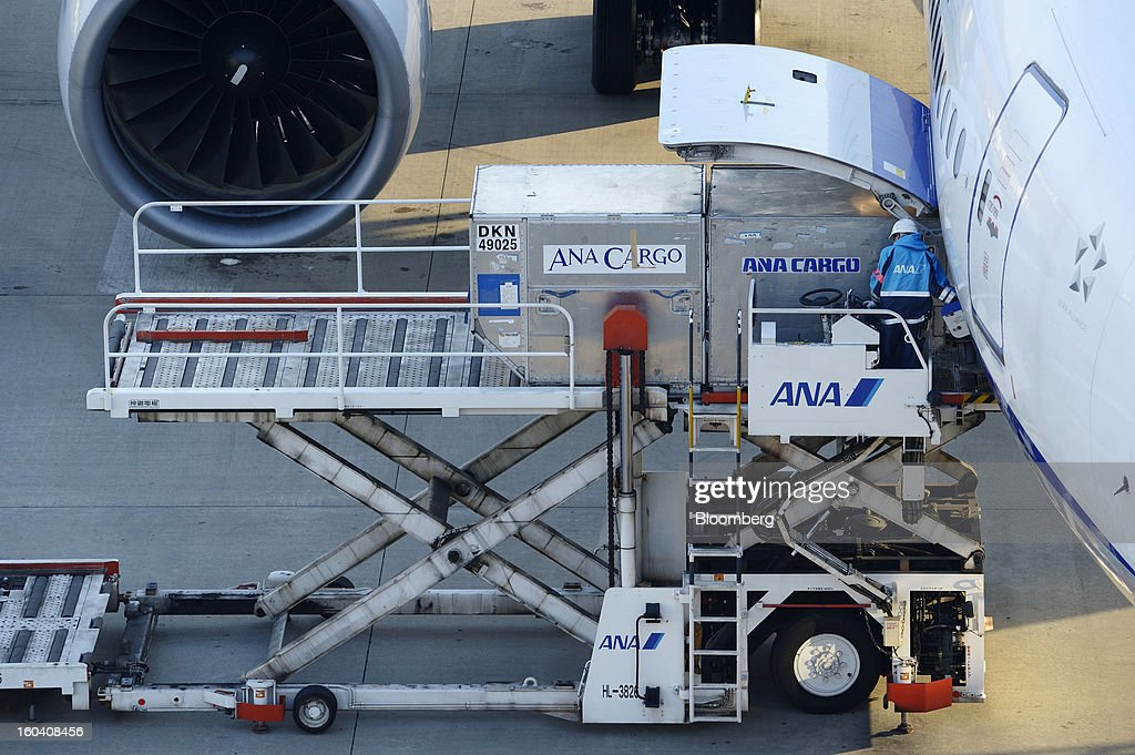 A member of All Nippon Airways Co.'s ground staff loads cargo containers onto an aircraft at Haneda Airport in Tokyo, Japan, on Wednesday, Jan. 30, 2013. ANA has canceled a total of 784 flights, affecting 74,200 passengers through Feb. 12, since a Jan. 16 incident that led to the global grounding of Boeing Co. 787s, according to figures from the company. Photographer: Akio Kon/Bloomberg via Getty Images