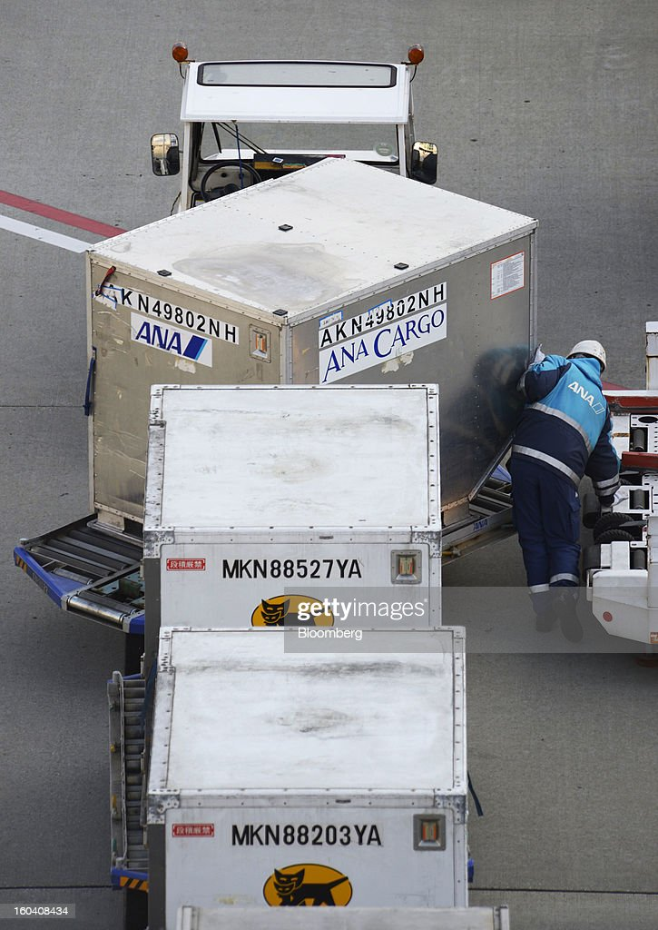A member of All Nippon Airways Co.'s ground staff prepares cargo containers for loading onto an aircraft at Haneda Airport in Tokyo, Japan, on Wednesday, Jan. 30, 2013. ANA has canceled a total of 784 flights, affecting 74,200 passengers through Feb. 12, since a Jan. 16 incident that led to the global grounding of Boeing Co. 787s, according to figures from the company. Photographer: Akio Kon/Bloomberg via Getty Images