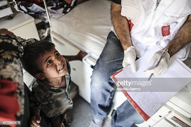 A member of Alliance of International Doctors gives medical treatment to Syrian refugees who wait at Akcakale Border gate to return their country as...