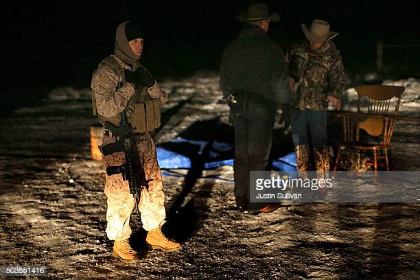 A member of an antigovernment militia holds an assault rifle as he stands guard at a checkpoint in front of the Malheur National Wildlife Refuge...