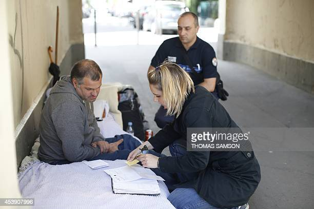 A member of an Assistance Unit to Homeless People of Paris' Prevention and Protection service meet homeless people flanked by a social worker on...