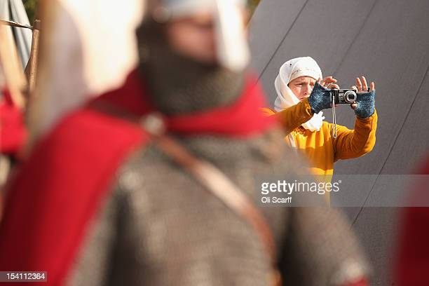 A member of an historical reenactment group photographs the Norman soldiers in their encampment before the annual reenactment of the Battle of...
