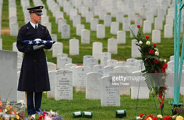 A member of an honor guard holds an American flag as he waits for the funeral of US Army Sergeant First Class Wilbert Davis at Arlington National...