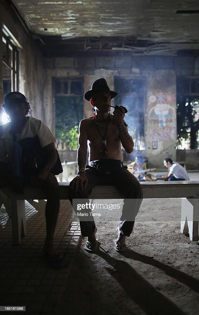 A member of an indigenous community smokes in the Aldeia Maracana building they are occupying, next to Maracana Stadium, the site of the 2014 World Cup finals, on October 17, 2013 in Rio de Janeiro, Brazil. The fading Aldeia Maracana used to house the Museum of Indian Culture before deteriorating and becoming occupied by squatting indigenous members in 2006. The building was slated for destruction ahead of the 2014 World Cup and the community was forcibly evicted in March. However, the community has managed to return and thus far have successfully battled to save the structure, which they hope to convert into an indigenous university. Indigenous groups throughout Brazil are battling the Brazilian government over land rights and other issues.
