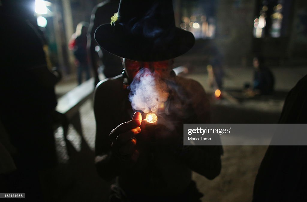 A member of an indigenous community smokes in the Aldeia Maracana building they are occupying next to Maracana Stadium, the site of the 2014 World Cup final, on October 17, 2013 in Rio de Janeiro, Brazil. The fading Aldeia Maracana used to house the Museum of Indian Culture before deteriorating and becoming occupied by squatting indigenous members in 2006. The building was slated for destruction ahead of the 2014 World Cup and the community was forcibly evicted in March. However, the community has managed to return and thus far have successfully battled to save the structure, which they hope to convert into an indigenous university. Indigenous groups throughout Brazil are battling the Brazilian government over land rights and other issues.