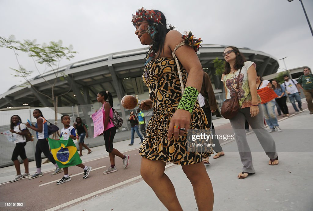A member of an indigenous community (C) walks to the Aldeia Maracana building they are occupying next to Maracana Stadium (Top L), the site of the 2014 World Cup finals, while giving a tour of the area to visitors on October 17, 2013 in Rio de Janeiro, Brazil. The fading Aldeia Maracana used to house the Museum of Indian Culture before deteriorating and becoming occupied by squatting indigenous members in 2006. The building was slated for destruction ahead of the 2014 World Cup and the community was forcibly evicted in March. However, the community has managed to return and thus far have successfully battled to save the structure, which they hope to convert into an indigenous university. Indigenous groups throughout Brazil are battling the Brazilian government over land rights and other issues.