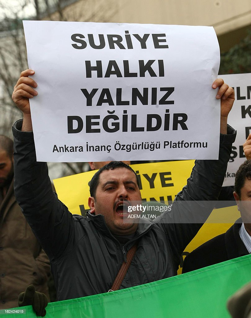 A member of an Islamic rights group hold a banner that read 'We are with Syrian people' as they stage a protest against Iran for its support to the Syrian regime, outside the Iranian embassy in Ankara, on February 23, 2013.