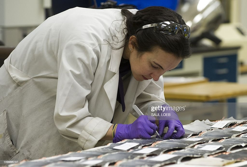A member of an NTSB investigation team examines pieces of damaged electrode coils from a battery cell that resulted in a fire aboard a Japan Airlines (JAL) Boeing 787 Dreamliner airplane at Logan International Airport in Boston earlier this month as she works inside an investigation lab at National Transportation Safety Board (NTSB) Headquarters in Washington, DC, on January 24, 2013. The state-of-the-art composite aircraft continues to be grounded as the investigation into the cause of the thermal damage continues. AFP PHOTO / Saul LOEB
