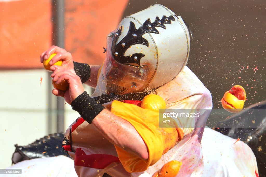 A member of an orange battle team is hit by oranges during the traditional 'battle of the oranges' held during the carnival in Ivrea, near Turin, on February 10, 2013. During the event which marks the people's rebellion against tyrannical lords who ruled the town in the Middle Ages, revellers parading on floats represent guards of the tyrant, while those on foot the townsfolk. AFP PHOTO / GIUSEPPE CACACE