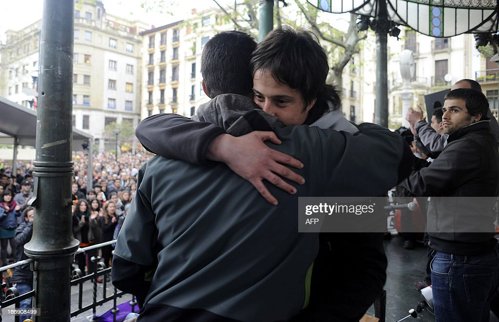 Member of Basque pro-independence youth organization SEGI Oier Lorente (R) hugs Adur Fernandez (L) after delivering a speech in the northern Spanish Basque city of San Sebastian on April 18, 2013. Hundreds of people remain gathered on the Boulevard of San Sebastian, to prevent the incarceration of eight members of SEGI sentenced to six years in prison by the Supreme Court. The Spanish Court issued arrest warrants on April 16 against Mikel Arretxe, Imanol Vicente, Naikari Otaegi, Egoi Alberdi, Aitor Olaizola, Adur Fernandez, Oier Lorente y Ekaitz Ezkerra for membership in an organized armed group.