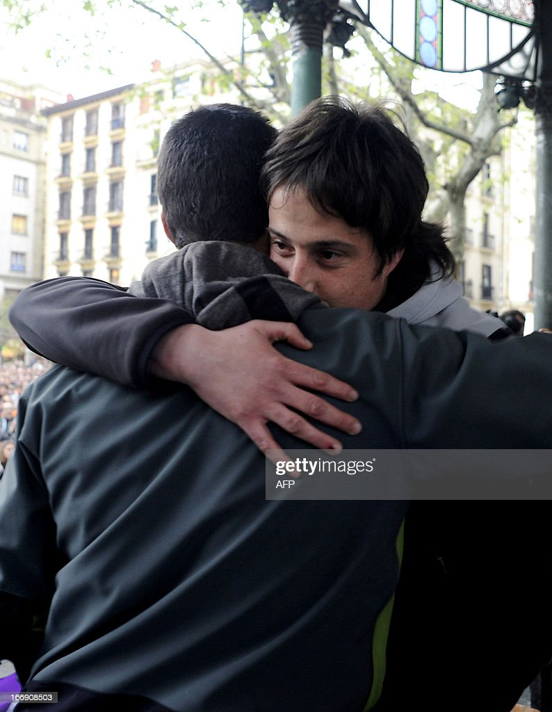 Member of Basque pro-independence youth organization SEGI Oier Lorente (R) hugs Adur Fernandez (L) after delivering a speech in the northern Spanish Basque city of San Sebastian on April 18, 2013. Hundreds of people remain gathered on the Boulevard of San Sebastian, to prevent the incarceration of eight members of SEGI sentenced to six years in prison by the Supreme Court. The Spanish Court issued arrest warrants on April 16 against Mikel Arretxe, Imanol Vicente, Naikari Otaegi, Egoi Alberdi, Aitor Olaizola, Adur Fernandez, Oier Lorente y Ekaitz Ezkerra for membership in an organized armed group. AFP PHOTO / ANDER GILLENEA