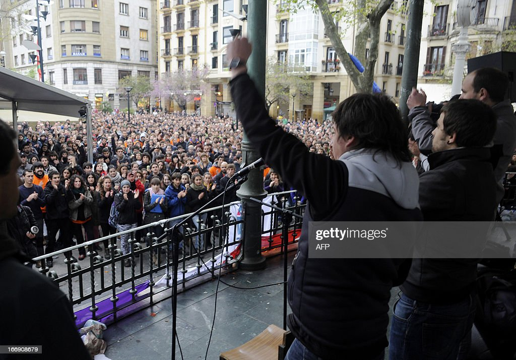 Member of Basque pro-independence youth organization SEGI Oier Lorente (C) raises his fist after delivering a speech in the northern Spanish Basque city of San Sebastian on April 18, 2013. Hundreds of people remain gathered on the Boulevard of San Sebastian, to prevent the incarceration of eight members of SEGI sentenced to six years in prison by the Supreme Court. The Spanish Court issued arrest warrants on April 16 against Mikel Arretxe, Imanol Vicente, Naikari Otaegi, Egoi Alberdi, Aitor Olaizola, Adur Fernandez, Oier Lorente y Ekaitz Ezkerra for membership in an organized armed group.