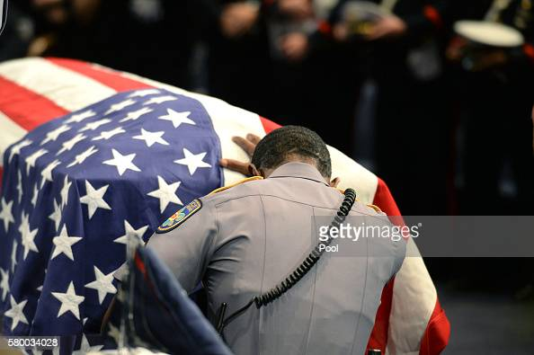 A member of Baton Rouge police corporal Montrell Jackson's unit kneels and touches his casket during his funeral at the Living Faith Christian Center...