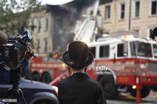 Member of 'black hat' Hasidic community watches fire fighters from press area Fire companies NYPD Red Cross and other emergency response personnel...