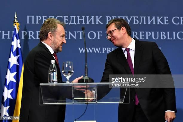 Member of Bosnia and Herzegovina's tripartite Presidency Bakir Izetbegovic shakes hands with Serbian President Aleksandar Vucic during their joint...