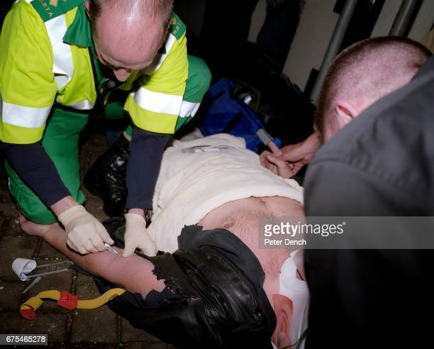 A member of Bristol's rapid response medical team attends to a man suspected of being intoxicated who has fallen from scaffolding November 2001