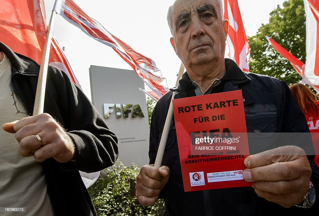A member of Building and Wood Workers' International (BWI) and Swiss Unia unions holds a red card reading 'A red card for FIFA, no World Cup without labour rights' during a demonstration outside the headquarters of the world's football governing body FIFA in Zurich on October 3, 2013. The protest came amid a report by Britain's Guardian saying that dozens of Nepalese construction workers treated like 'slaves' have died working at World Cup projects in Qatar in recent weeks. In 2010 Qatar won the right to host the 2022 FIFA World Cup. The FIFA executive committee is meeting in Zurich to discuss the tournament's timetable after calls for it to be staged in winter because of the desert emirate's scorching summer. AFP PHOTO / FABRICE COFFRINI