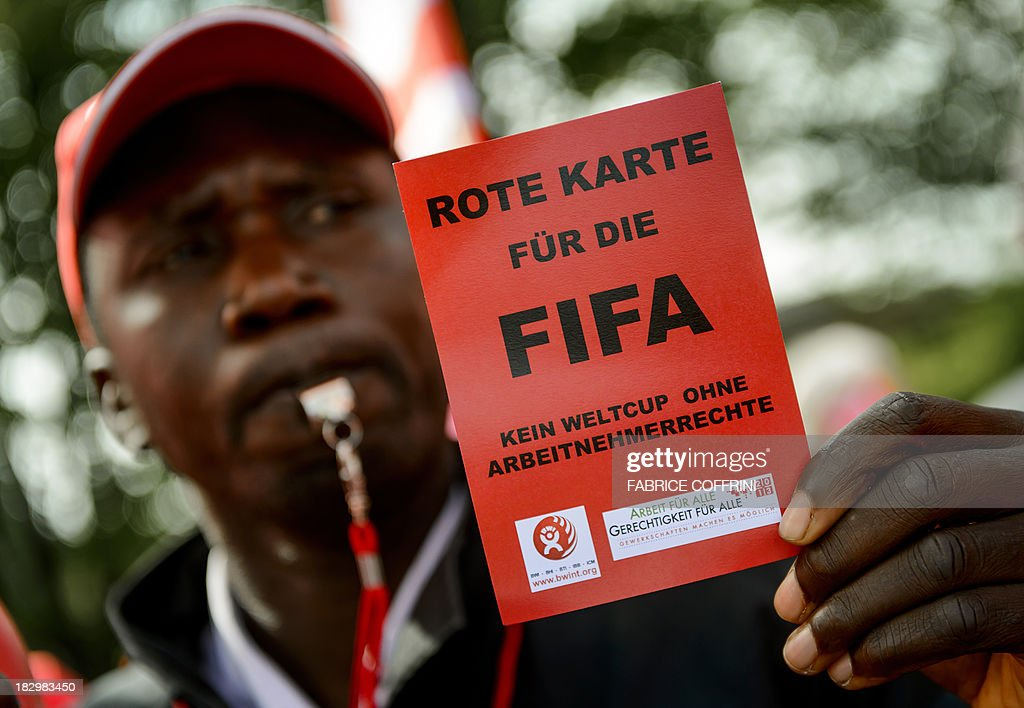 A member of Building and Wood Workers' International (BWI) and Swiss Unia unions holds a red card reading 'A red card for FIFA, no World Cup without labour rights' during a demonstration outside the headquarters of the world's football governing body FIFA in Zurich on October 3, 2013. The protest came amid a report by Britain's Guardian saying that dozens of Nepalese construction workers treated like 'slaves' have died working at World Cup projects in Qatar in recent weeks. In 2010 Qatar won the right to host the 2022 FIFA World Cup. The FIFA executive committee is meeting in Zurich to discuss the tournament's timetable after calls for it to be staged in winter because of the desert emirate's scorching summer.