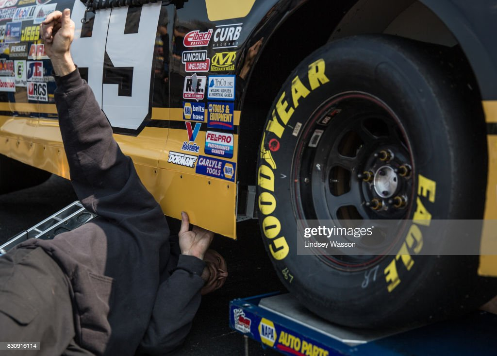 A member of Chris Eggleston #99's crew checks under the vehicle during final practice before the NASCAR K&N Pro Series West NAPA Auto Parts 150 on August 12, 2017 at Evergreen Speedway in Monroe, Washington.