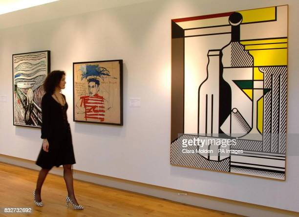 A member of Christies staff walks past 'The Scream ' by Andy Warhol 'Untitled ' by JeanMichel Basquiat and 'Purist Painting with Bottles' by Roy...