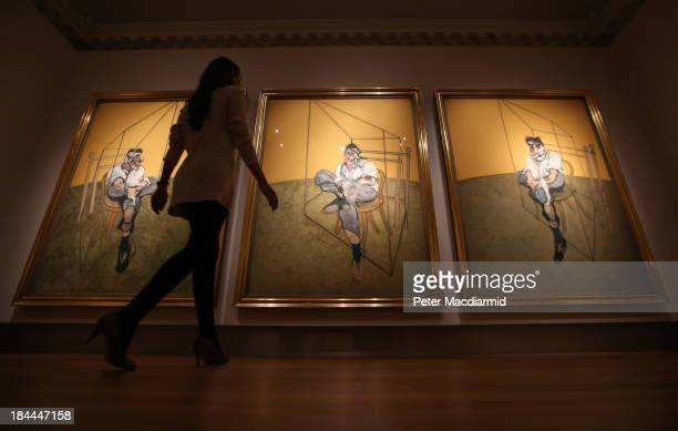 A member of Christie's staff walks towards Francis Bacon's 'Three Studies of Lucien Freud' on October 14 2013 in London England The work forms part...
