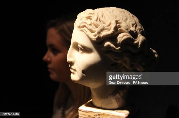 A member of Christie's staff with a Roman Marble Female head with an estimate of 1500020000 which is part of a collection of antiquities called the...