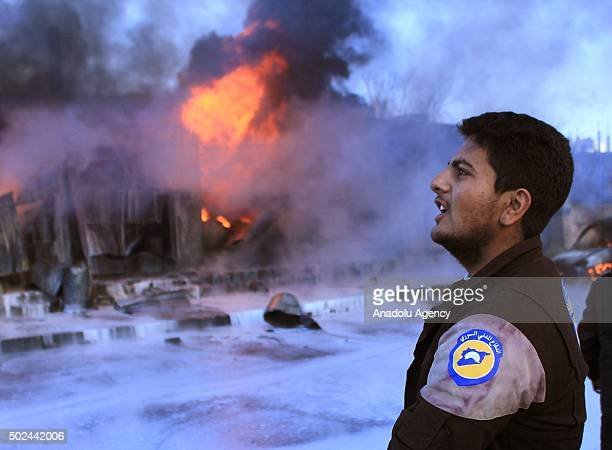 A member of civil defense team is seen as flames rise after the war crafts belonging to the Russian army carried out airstrikes on two hospital in...