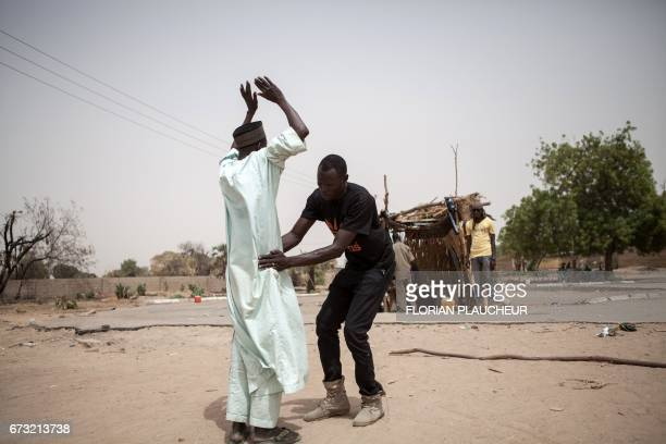 TOPSHOT A member of Civilian Joint Task Force screens an old person at the entrance of the town of Damasak in North East Nigeria on April 25 2017 as...