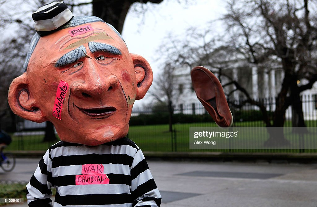 A member of Code Pink dressed as President George W Bush is hit with a shoe during a protest in front of the White House December 17 2008 in...