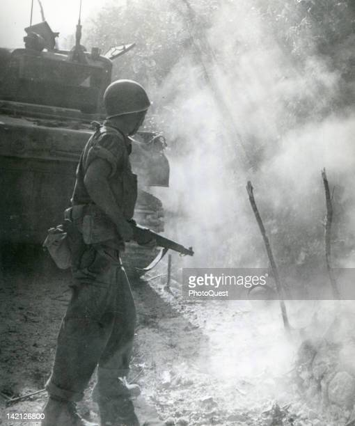 A member of Company L 24th Infantry 24th Division aims his gun into the smoke at the helmet of a Japanese soldier during the battle of Malinta Hill...