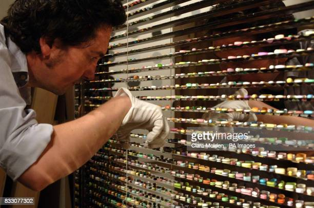 A member of Damien Hirst's production team 'Science' painstakingly places into a cabinet some of the 6136 handcast and painted bronze pharmaceutical...