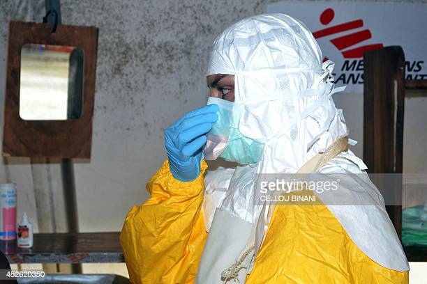 A member of Doctors Without Borders puts on protective gear at the isolation ward of the Donka Hospital on July 23 2014 in Conakry A Liberian man has...