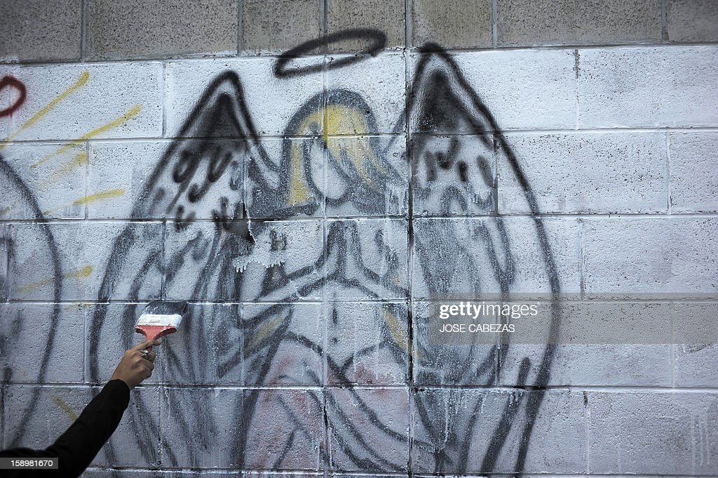 A member of El Camino Christian Church erases a 'Mara Maquina' gang graffiti at Chintu neighborhood in Apopa, 14 km north of San Salvador, El Salvador on January 4, 2013. Graffitis started to be erased as Raul Mijango, Gang truce mediator, announced that 18 districs in El Salvador will be considered 'Sanctuary Territories' for gangs as a second stage of the gang truce. AFP PHOTO/ Jose CABEZAS