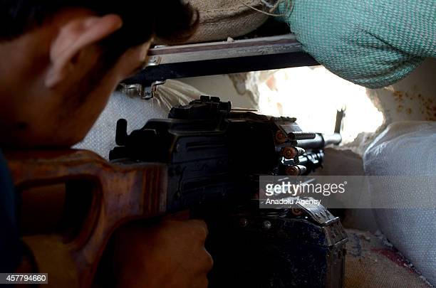 A member of Free Syrian Army takes positions from a hole of house during the clashes between the Free Syrian Army and Assad regime forces in Cobar...