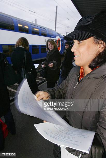 A member of French association of urban transport passengers delivers leaflets 13 November 2007 at the train station of ManteslaJolie while...