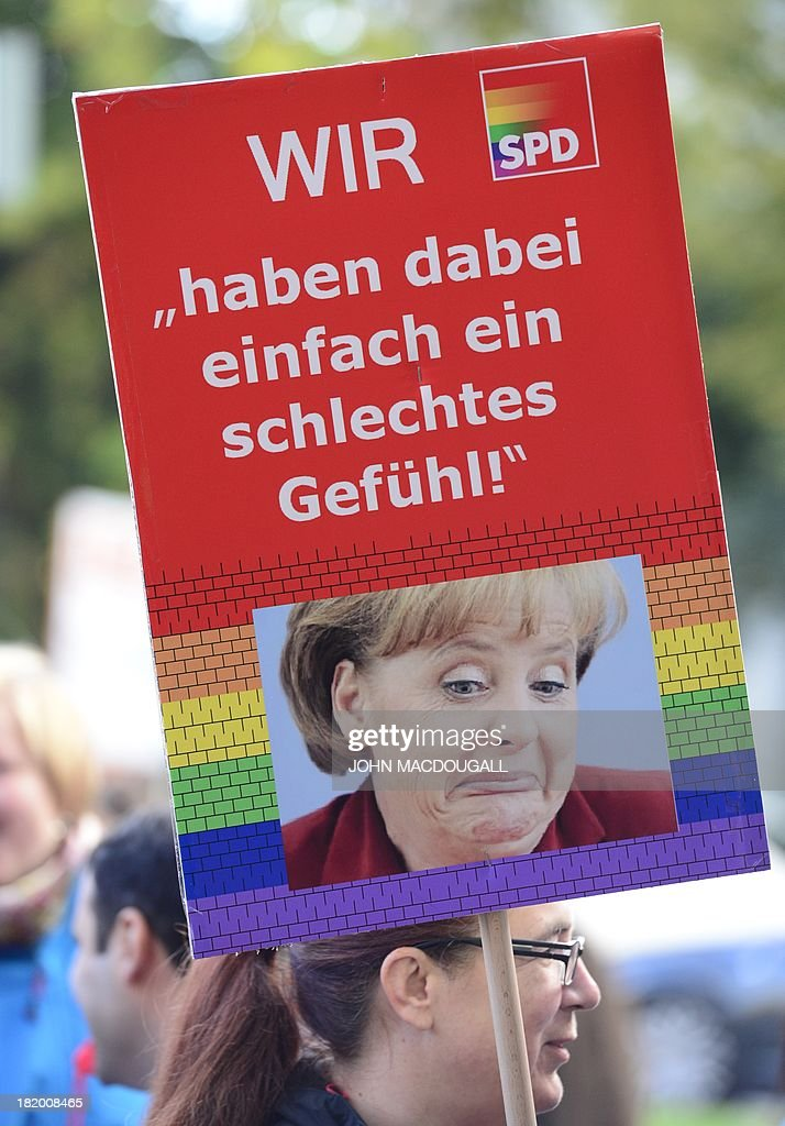 A member of German Social Democratic Party (SPD) holds a poster displaying a photo of German Chancellor Angela Merkel, the rainbow colours and reading 'We have a bad feeling' while demonstrating in front of the SPD's headquarters on September 27, 2013 where a meeting on a 'grand coalition' takes place. Germany's opposition Social Democrats hold a mini-party conference to discuss behind closed doors overtures by Chancellor Angela Merkel for a left-right 'grand coalition' after her conservatives won weekend elections but fell short of an outright majority MACDOUGALL
